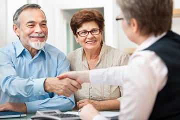 Mature couple shaking hands with a broker