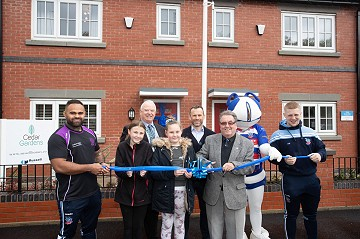 Photograph of children, Hornets players and VIPs cutting the ribbon at Cedar Gardens in Heywood