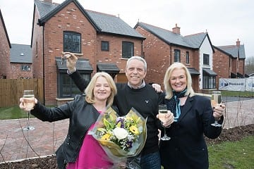 Couple with sales consultant outside their new home